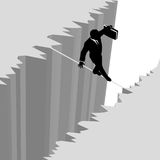 Business man on risk tightrope over cliff danger. A business man takes a risky dangerous walk on a tightrope over a cliff drop off to safety Stock Photography