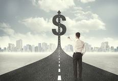 Business man on road heading toward a dollar sign. Concept Stock Images