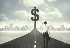Business man on road heading toward a dollar sign Stock Images