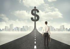 Business man on road heading toward a dollar sign Stock Photo