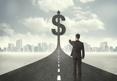 Business man on road heading toward a dollar sign royalty free stock photo