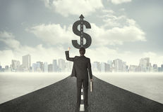 Business man on road heading toward a dollar sign Royalty Free Stock Images