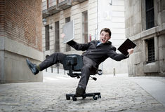 Business man rolling downhill on chair with computer and tablet Royalty Free Stock Photos