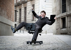 Business man rolling downhill on chair with computer and tablet. Happy crazy business man rolling downhill on chair with computer and tablet Royalty Free Stock Image