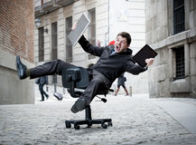 Business man rolling downhill on chair with computer and tablet. Happy crazy business man rolling downhill on chair with computer and tablet Royalty Free Stock Photo