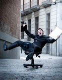 Business man rolling downhill on chair with computer and tablet Stock Photo