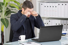 Business man rubs his eyes from the bad news at the office Stock Image
