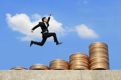 Business man run on money. Business concept - business man run and jump on money stairs with blue sky background, asian male stock images