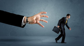 Business man running away from a huge hand concept Royalty Free Stock Photos