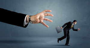 Business man running away from a huge hand concept Stock Photography