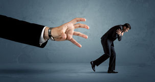 Business man running away from a huge hand concept Stock Photo