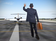 Business man running behind a plane Royalty Free Stock Images
