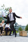 Business man running with businesspeople watching Royalty Free Stock Photos