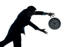 Business man running after clock silhouette Stock Image