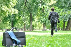 Business man running in park - escape. Escape from civilization concept - business man running in park away from bag, shoes and tie Stock Images