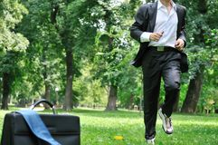 Business man running in park - training. Training - business man running in park, bag and tie laid on grass stock images