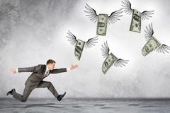 Business man running to catch flying dollars Stock Images