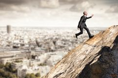 Business man running uphill from a rock Stock Images