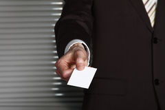 A business man's hand with a card. A business man in a brown suit hanging a white card Stock Photos