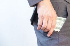 Business man's hand hiding money in pocket Stock Image