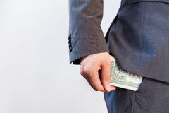 Business man's hand hiding money in pocket Stock Images