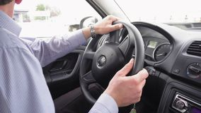Business man's hands driving a modern car. Close up of business man's hands driving a modern car, turning the steering wheel in slow motion. Business trip stock video footage