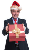 Business man in santa hat offering a present box royalty free stock image