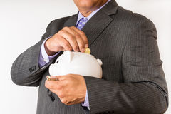 Business man saving some money. Man in a suit putting some change away in a piggybank. Stock Photo