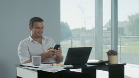 Business man scrolling mobile phone at work place. Smiling man having break. Business man scrolling mobile phone at remote work place. Smiling man having break stock video footage