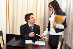 Business man and secretary having conversation. And giving her a  paper  in a meeting room Royalty Free Stock Images