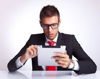 Business man selecting on his electronic pad. Amazed business man wearing glasses selecting something on his electronic pad Stock Photography