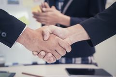 Business man shaking hand with woman clapping Stock Photo