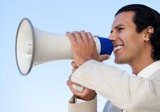 Business man shouting through a megaphone. Portrait of an Hispanic business man shouting through a megaphone against a blue sky background Stock Photos