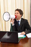 Business man shouting in megaphone. And sitting on chair in office Stock Photography