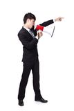 Business man shouting into a megaphone. Young business man shouting into a megaphone and finger point to up forward in full length isolated over a white Royalty Free Stock Image