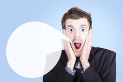 Business man shouting out urgent call to action. Portrait of an excited young business man with large blue eyes shouting out an urgent advertising message Royalty Free Stock Images