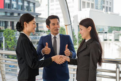 Business man show thumb up and two business woman shaking hands for demonstrating their agreement to sign agreement or contract Royalty Free Stock Photography