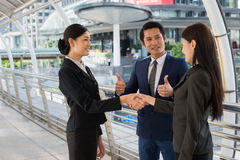 Business man show thumb up and two business woman shaking hands for demonstrating their agreement to sign agreement or contract  Stock Images