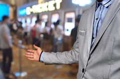 Business Man show welcome or invite gesture on Movie Ticket Syst Royalty Free Stock Photos
