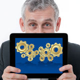 Business man showing 3D gear for collab. Business man showing a tablet with 3d gear for collaboration of business success Royalty Free Stock Image