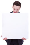 Business man showing blank signboard. Happy smiling young business man showing blank signboard, isolated on white background Royalty Free Stock Photo