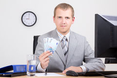 Business man showing money in bright office Royalty Free Stock Photos