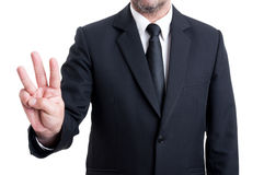 Business man showing number three with fingers. Elegant business man showing number three with fingers. Executive manager or entrepreneur gesture Royalty Free Stock Images