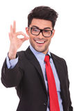 Business man showing ok sign. Portrait of a young business man showing ok sign with a large smile on his face, over white background royalty free stock photography