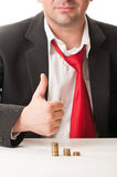 Business man showing ok sign with piles of coins Stock Images