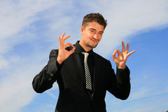Business man showing okay sign. Elegant man showing status of his efforts Royalty Free Stock Photography