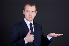 Business man showing something on his hand and thumbs up Stock Photos