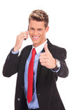 Business man showing thumbs up on phone Royalty Free Stock Image