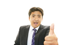 Business man showing thumbs up sign Stock Photos