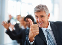 Business man showing thumbs up with staff behind Royalty Free Stock Photography